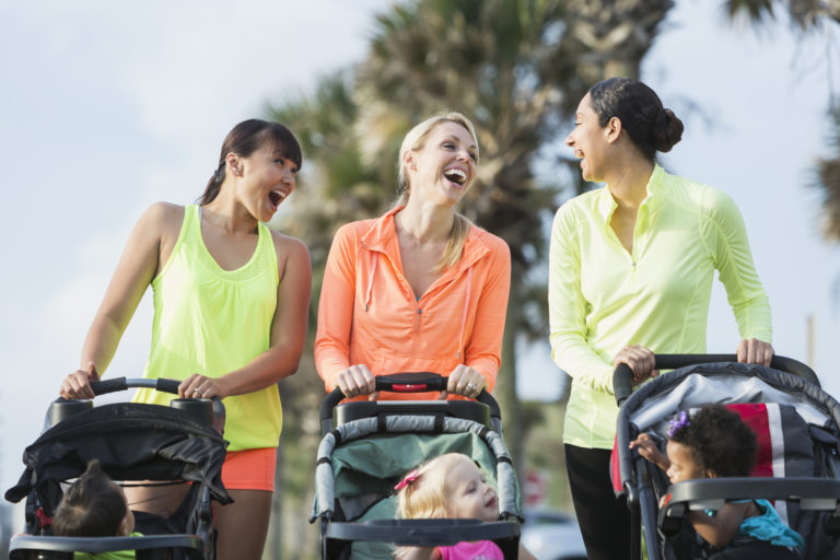 A group of three multi-ethnic mothers walking together, pushing their children in jogging strollers. The child on the left, a 22 month old toddler with blond hair, is the oldest. The African American girl and Asian boy are 11 months old.