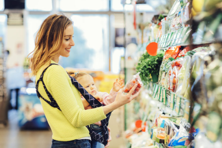 Mother shopping groceries with her baby daughter. She is choosing local organic vegetables. Smiling and enjoy shopping with her child.