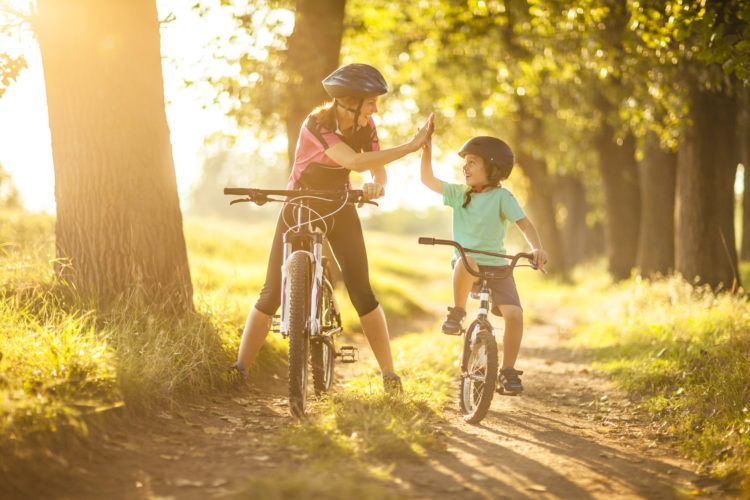 Happy family cycling in the countryside on a bright sunny day