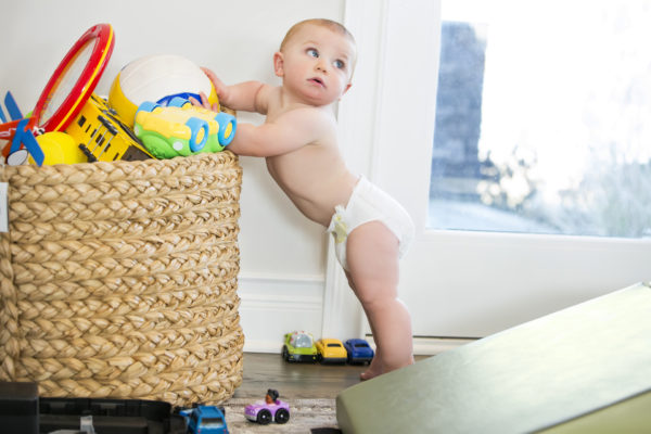 A baby boy, wearing only a diaper, tries to push over a basket of toys. Shot with Canon 5D Mark 3. rr