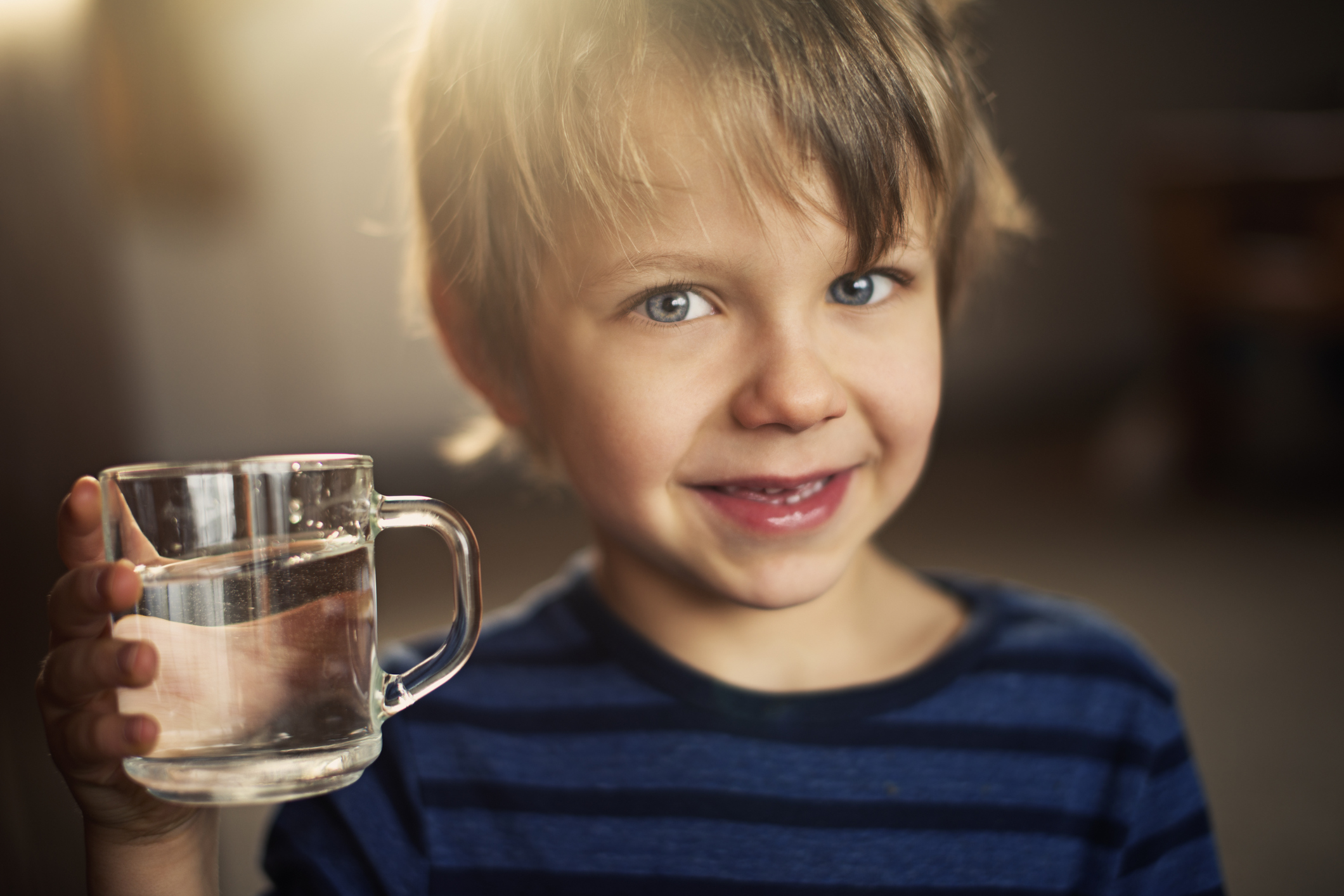 Closeup portrait of a little boy holding a glass of water. The boy is wearning blue blouse and smiling to the camera. The boy is aged 5 and is backlit by the morning sun from the window behind him.