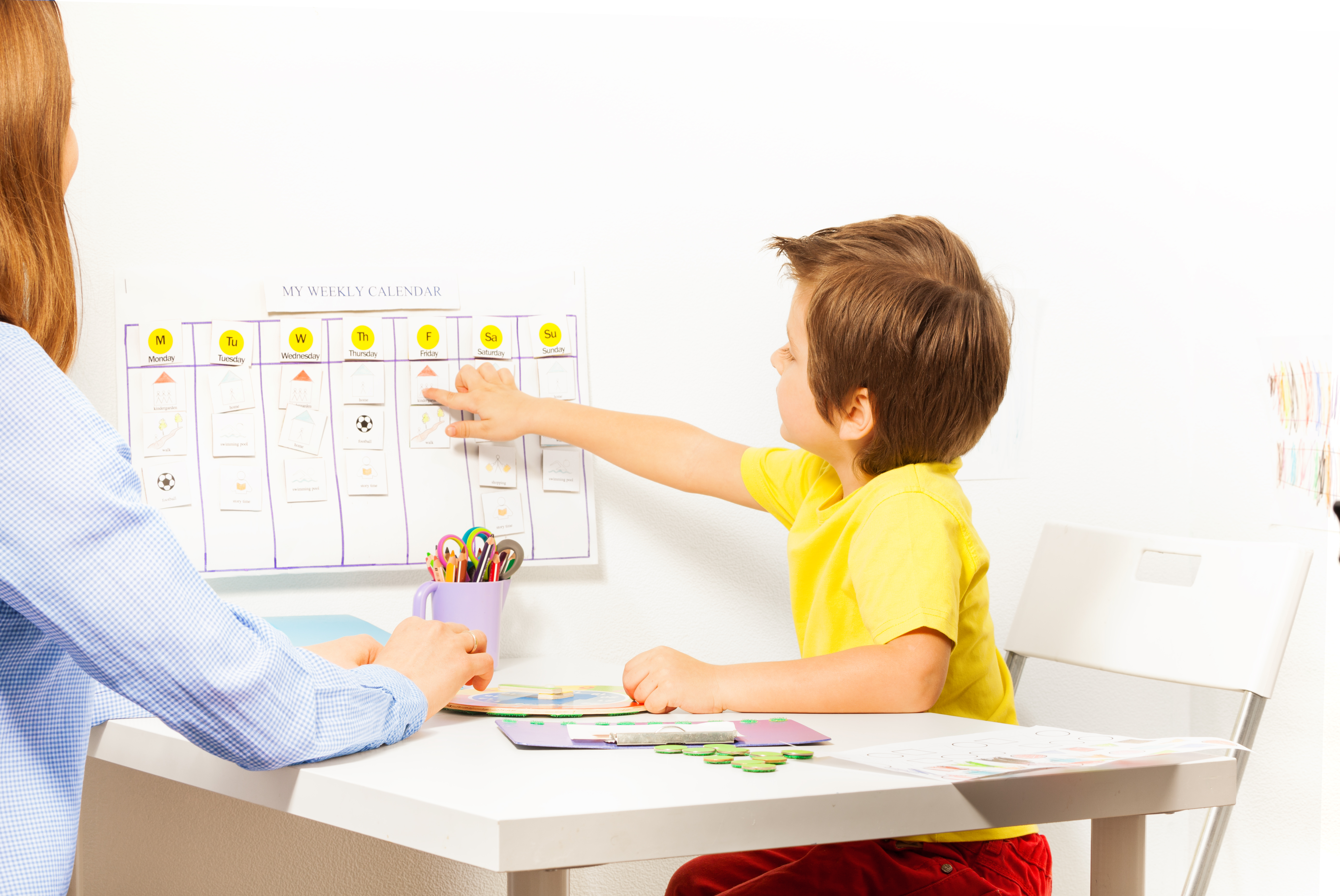 Boy pointing at the calendar on the wall with days and activities arranged developing game with his parent sitting opposite at the table indoors