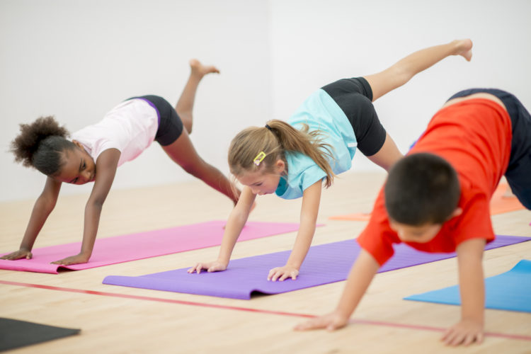 A multi-ethnic group of elementary age children are doing yoga together in the gym.