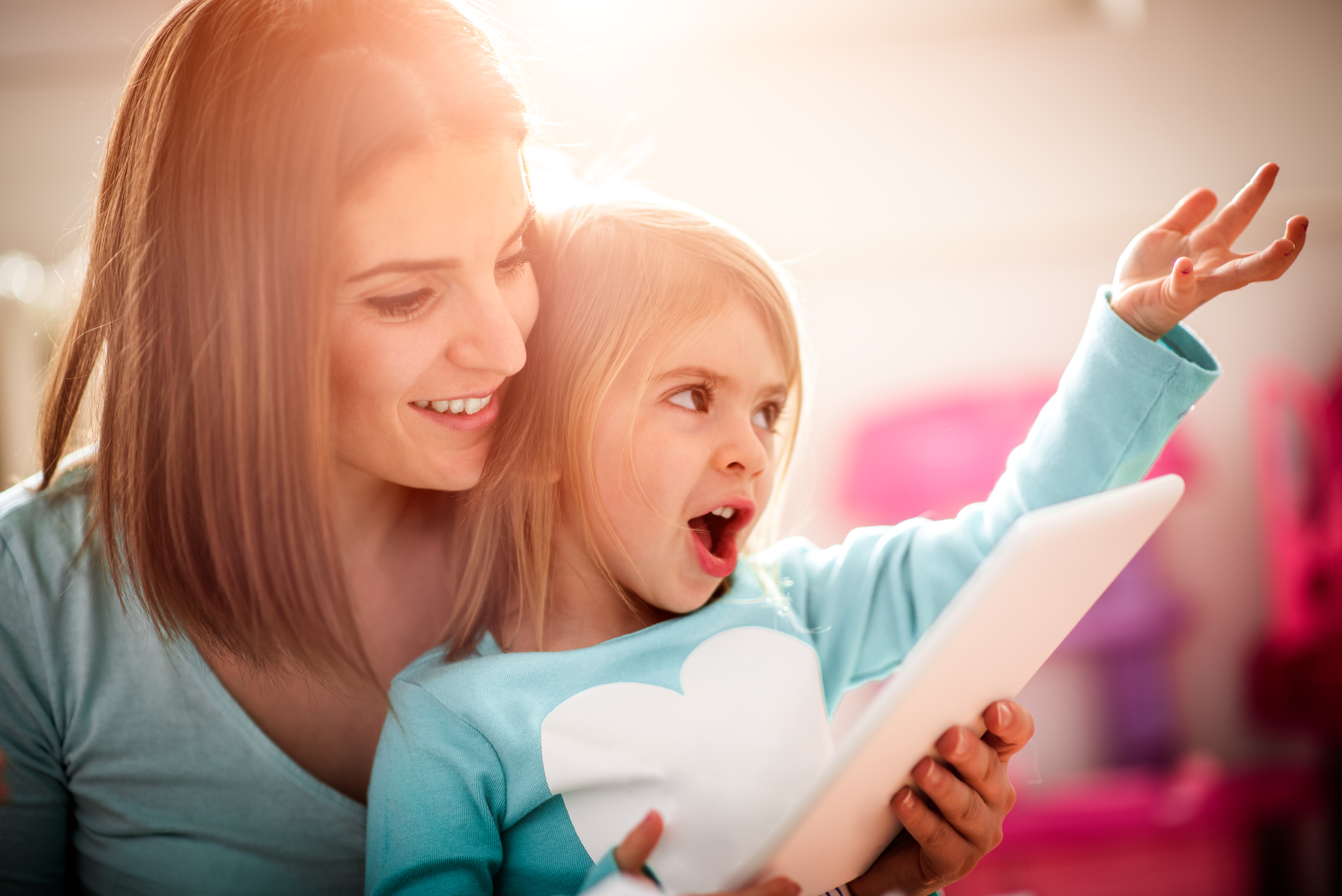 Mother is holding digital tablet and showing some multimedia content to her little daughter who is having a lot of fun. Bright light is coming through the window in the background.