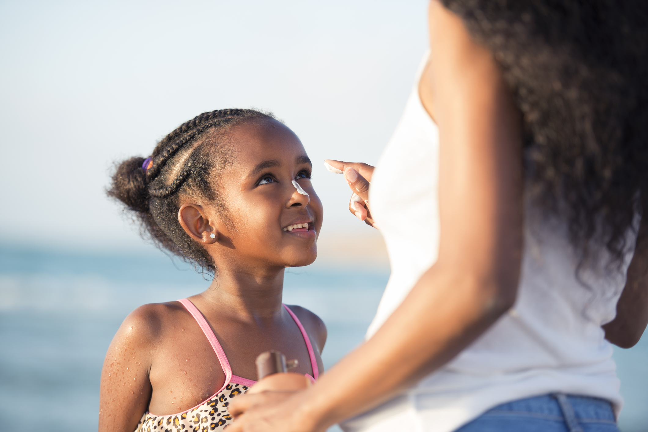 Mother applying sun protection to her 6 years daughter in the beach.