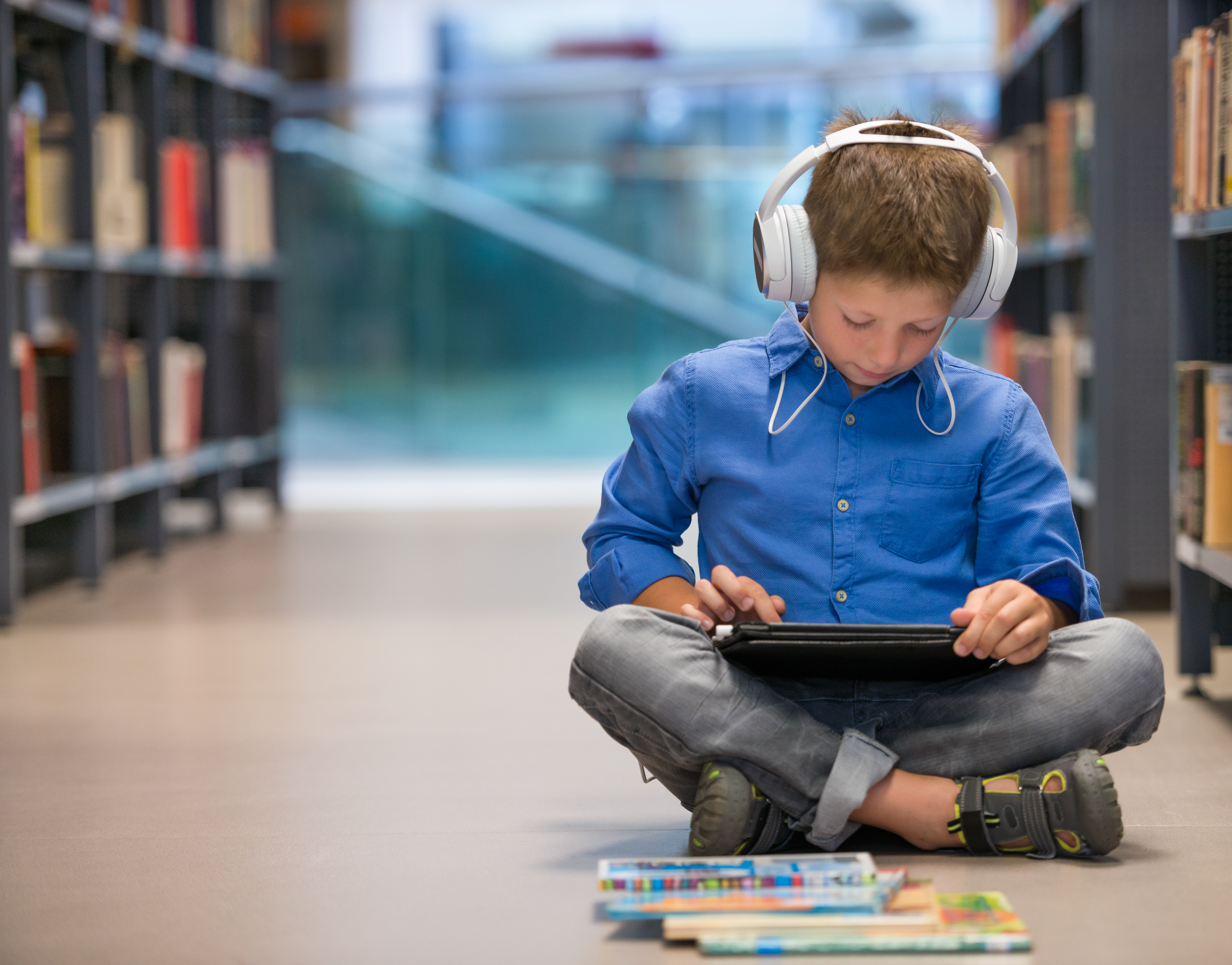 Schoolboy with headphones and tablet computer sitting on library floor.