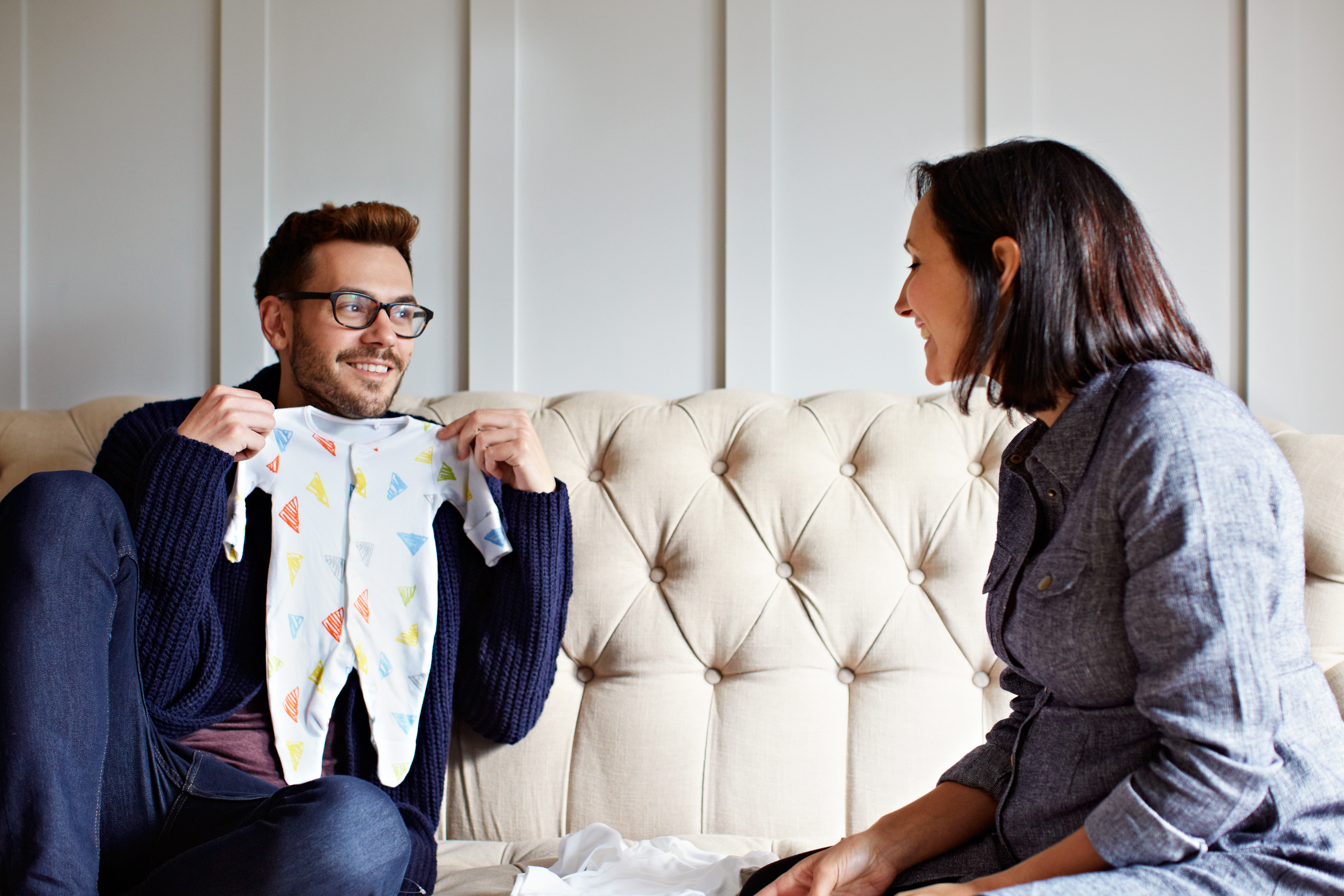 Shot of a young man showing his pregnant wife baby clothes on their sofa