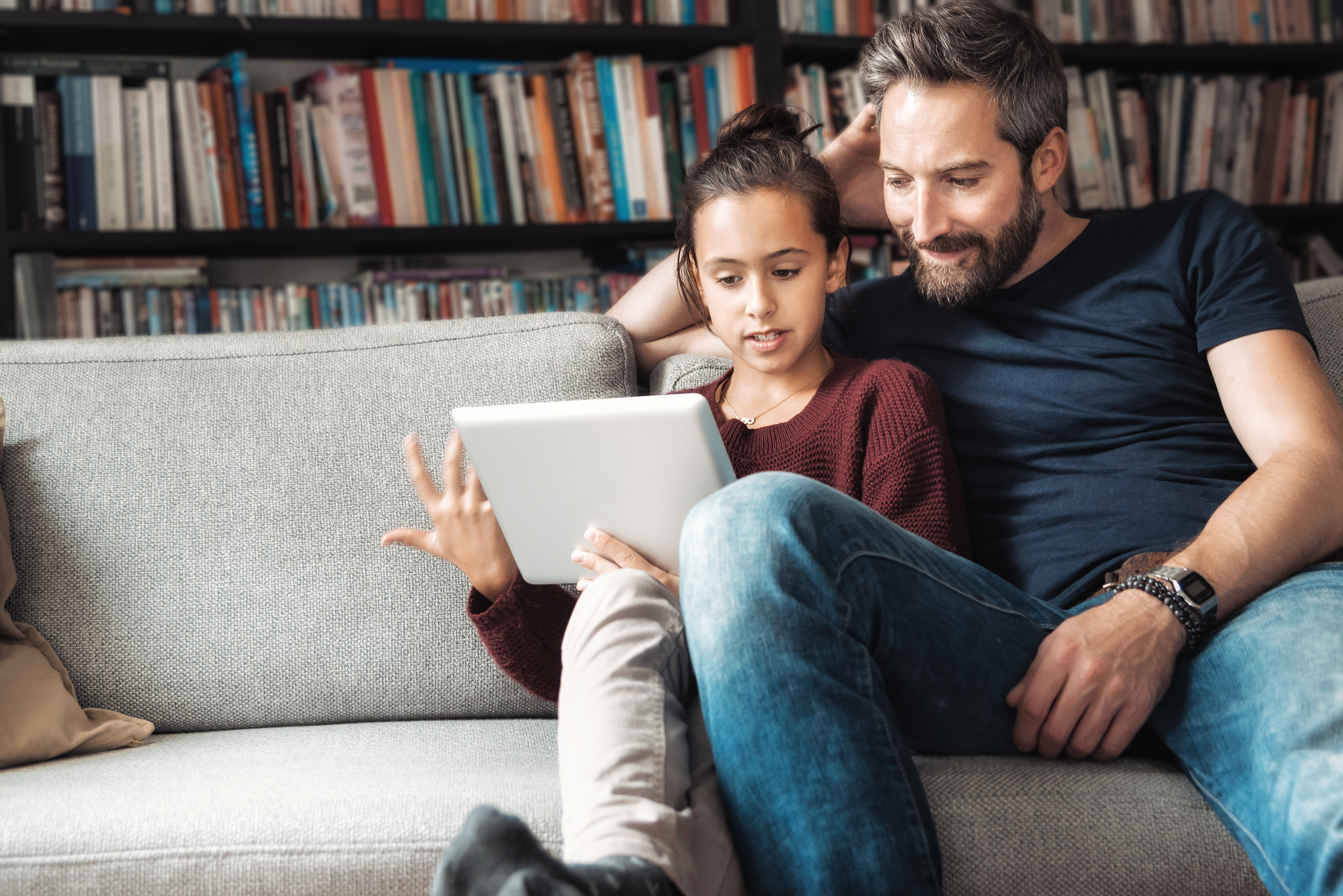 happy father and daughter having fun with digital tablet on couch
