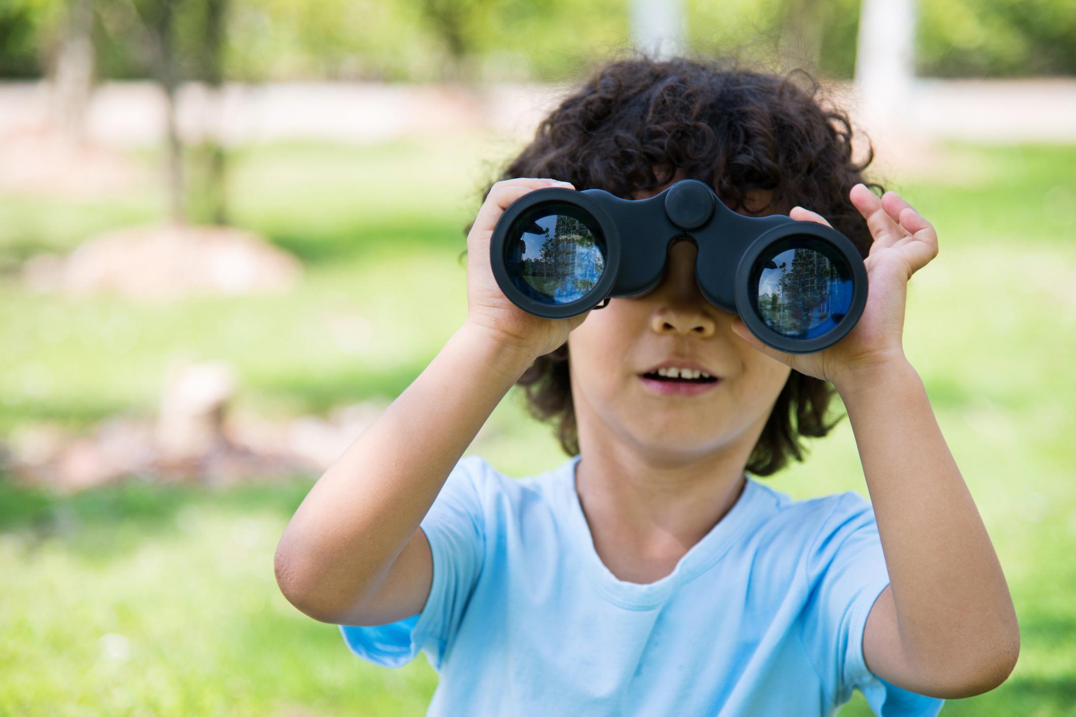 Little boy holding a binocular at park.