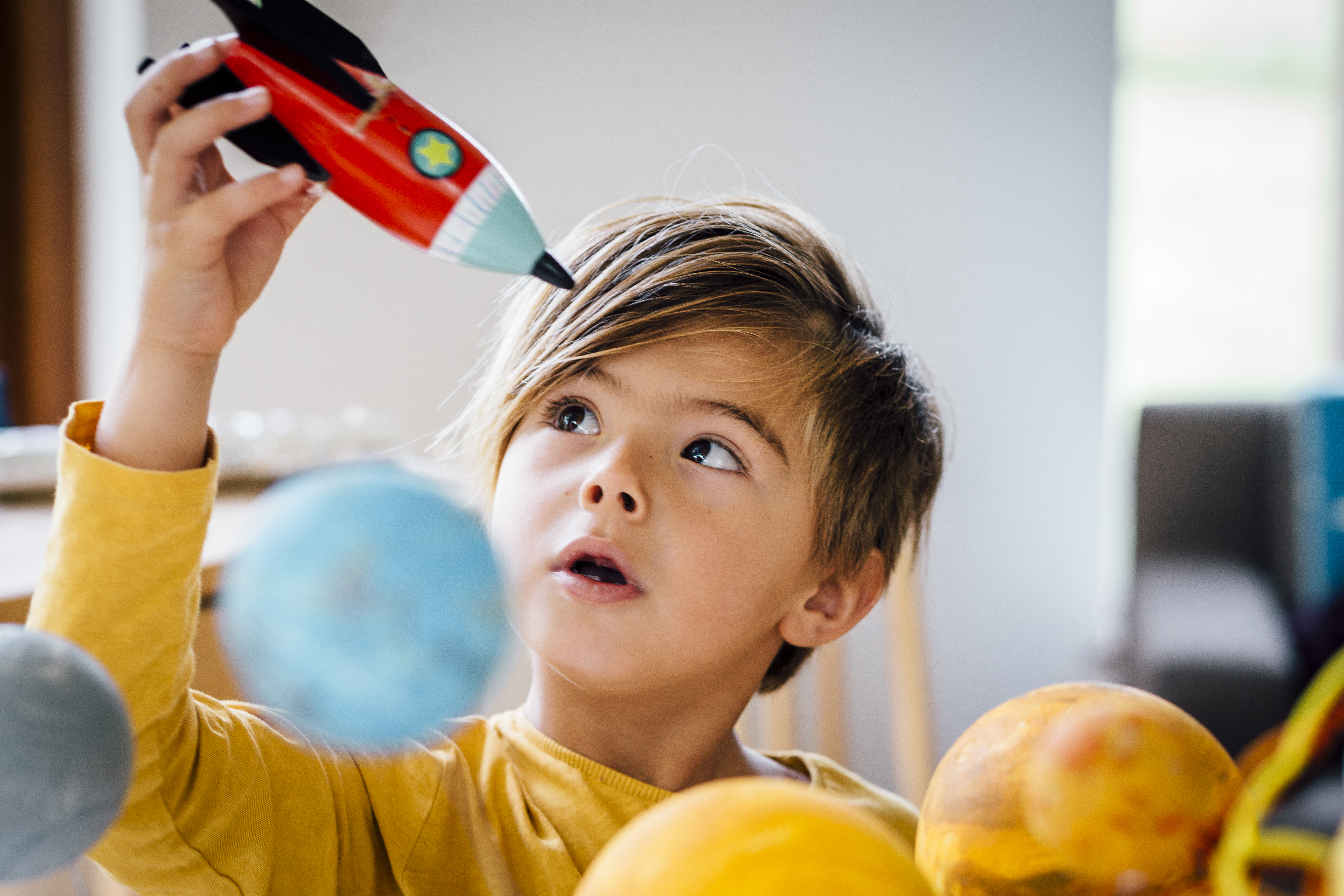 Little boy playing with his homemade planetarium as he holds a rocket with arms raised as he plays.