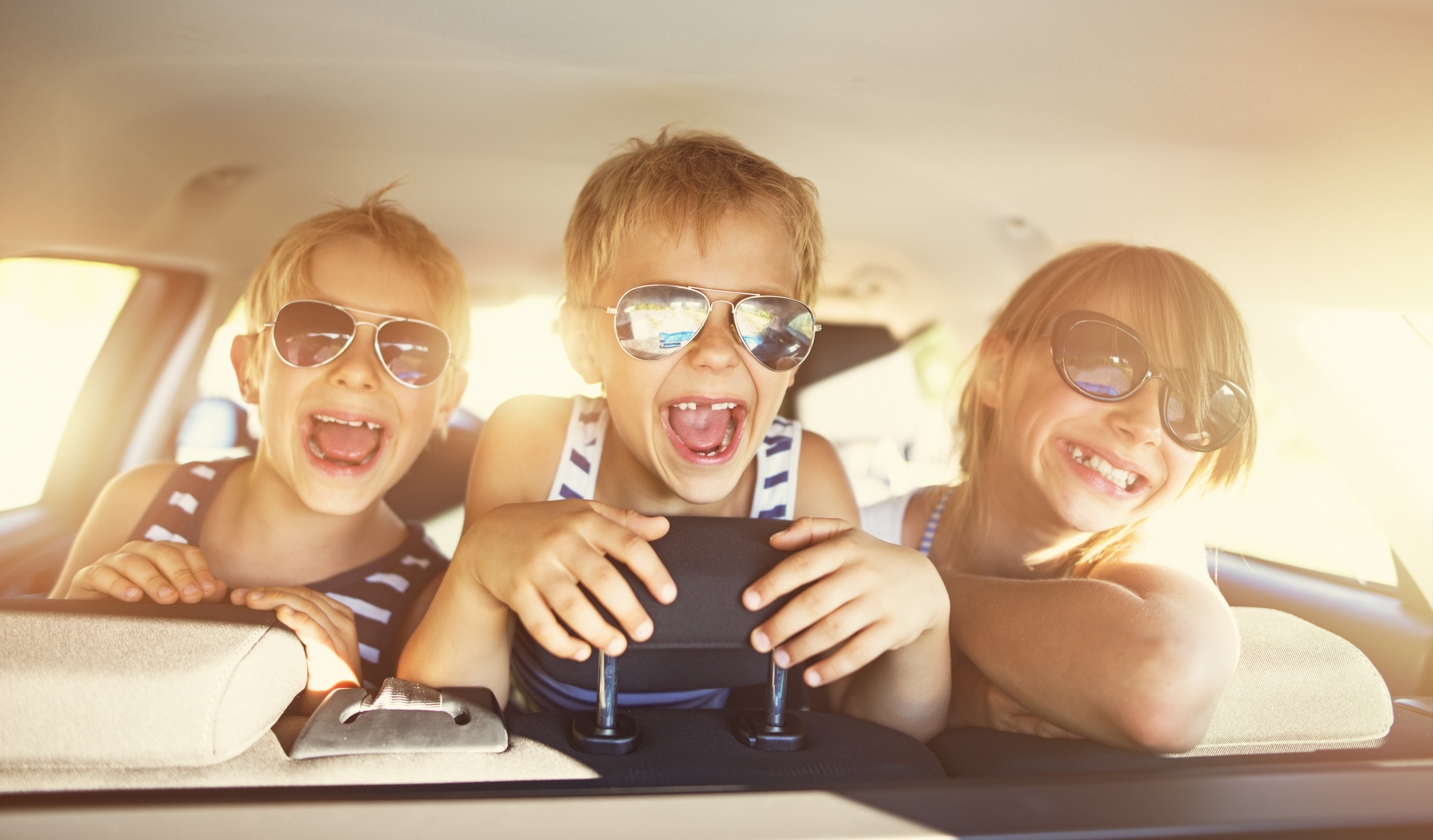 Three kids laughing in car on a road trip. Kids are aged 10 and 7. The kids are laughing and looking backward. Sunny summer day.