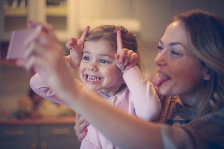 Little girl making self portrait with her mom.