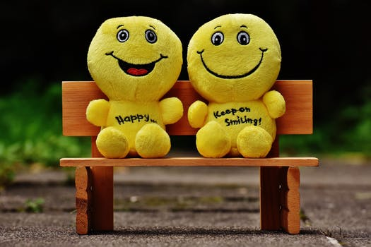 Smiley toys sitting on a bench