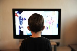 A picture of a child in front of a television