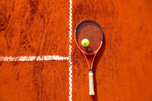 A picture of a Tennis racquet and ball resting on a clay court