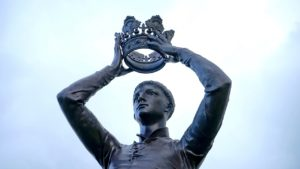 A picture of a statue holding a crown.