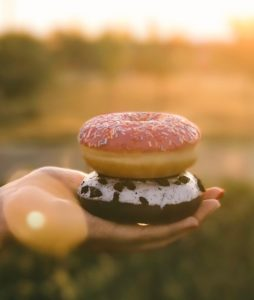 A picture of a hand holding two donuts