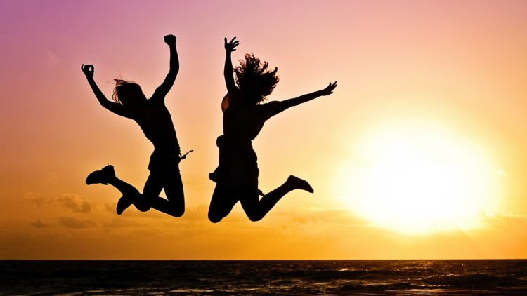 A picture of two women jumping because they do not have kids