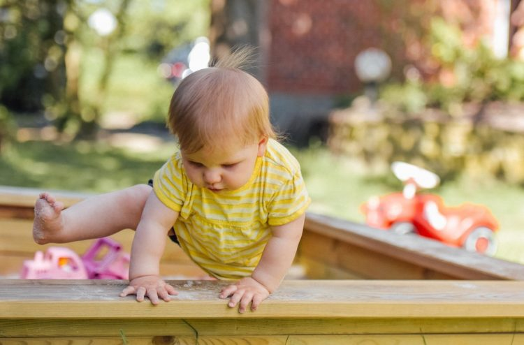 A picture of a baby climbing in a house that needs toddler-proofing