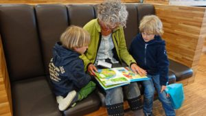 A picture of an adult reading to two children.