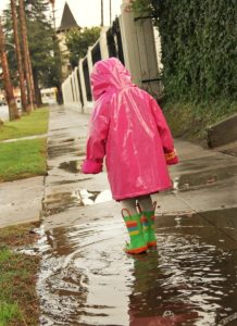 A picture of a child walking through a puddle