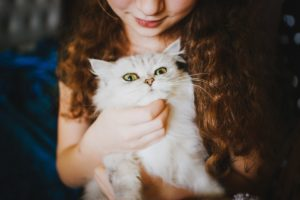 A picture of a young girl holding a cat