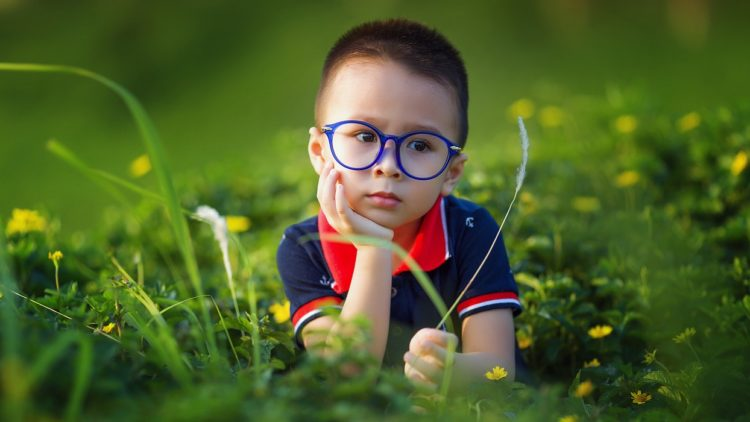 A picture of a child sitting in the grass and thinking about National Science Week