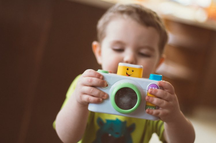 A picture of a child with a toy camera enjoying World Photo Day