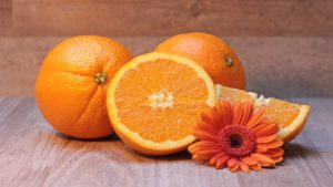 A picture of full and cut oranges