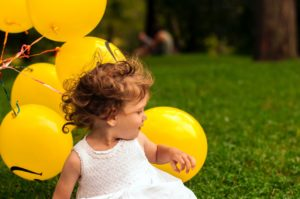 A picture of a child sitting on the grass surrounded by balloons