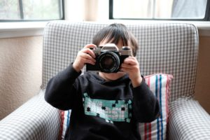 A photo of a young boy using a camera
