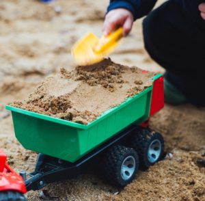 A picture of a child playing with a toy dump truck