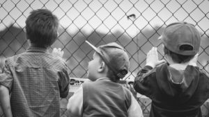 A picture of three young boys watching sport through a fence