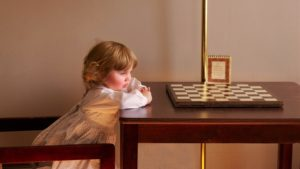A picture of a young girl looking at a chess board