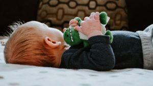 A picture of a baby sleeping on a bed with a dinosaur toy