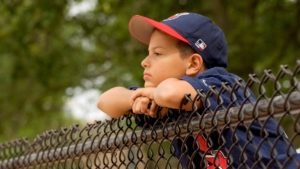 A picture of child watching sport over a fence.