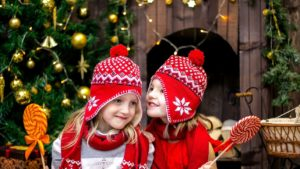 A picture of two young girls who are smiling about Christmas starting early