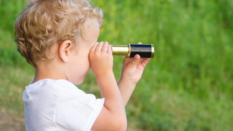 A picture of a child looking through a telescope because he has a pirate fascination