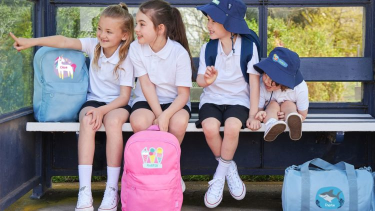 A picture of children in their school uniforms waiting for the bus