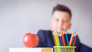 A picture of a child sitting next to some pencils