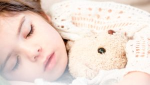 A picture of a child asleep with a teddy bear