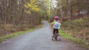 A picture of a young child riding a bike with training wheels