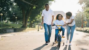 A picture of two parents teaching a child to ride a bike