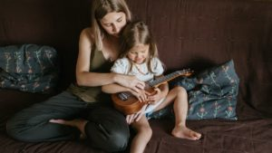 A picture of a woman teaching a child to play the ukulele