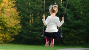 A picture of a young child playing on a swing