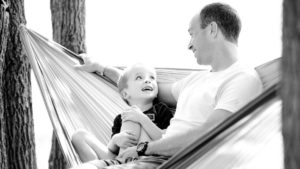 A picture of a father and son talking in a hammock