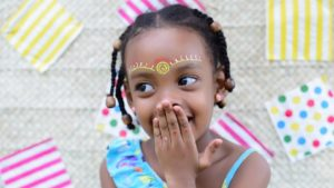 A picture of a young girl covering her laugh