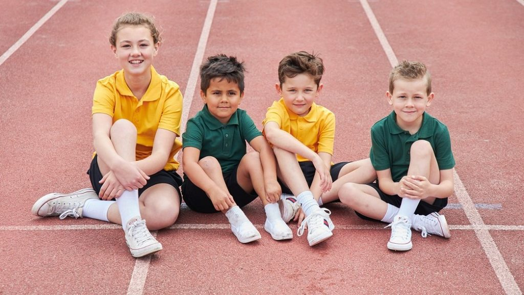 A picture of children sitting on an athletics track.