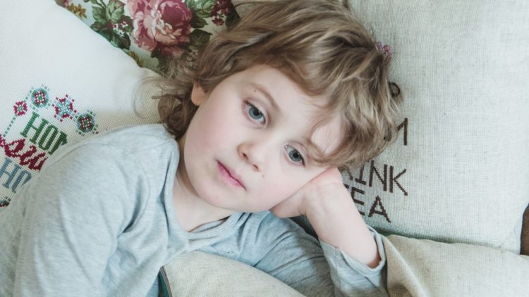 A picture of a child on a bed contemplating mindfulness