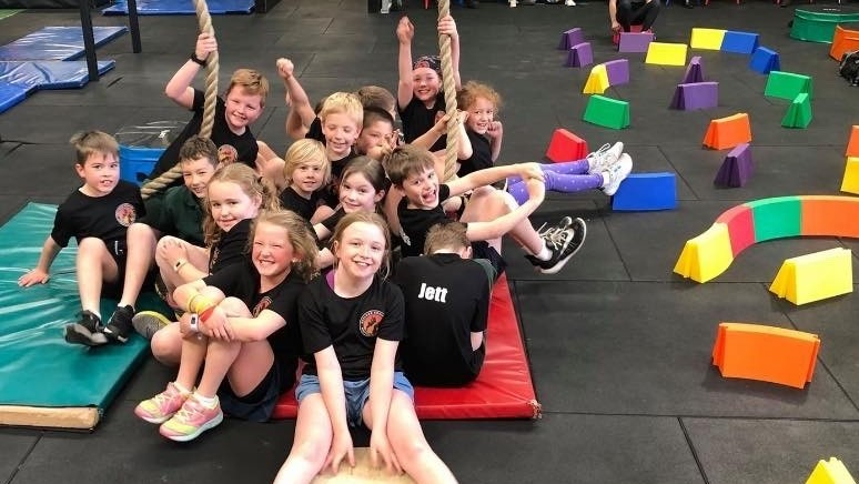 A picture of kids sitting in a gym